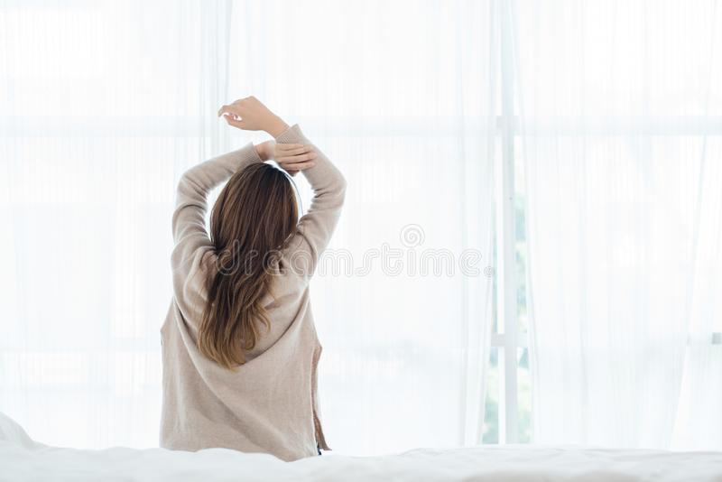 Opinião traseira a mulher asiática nova bonita feliz que acorda na manhã que olha através da janela fotografia de stock