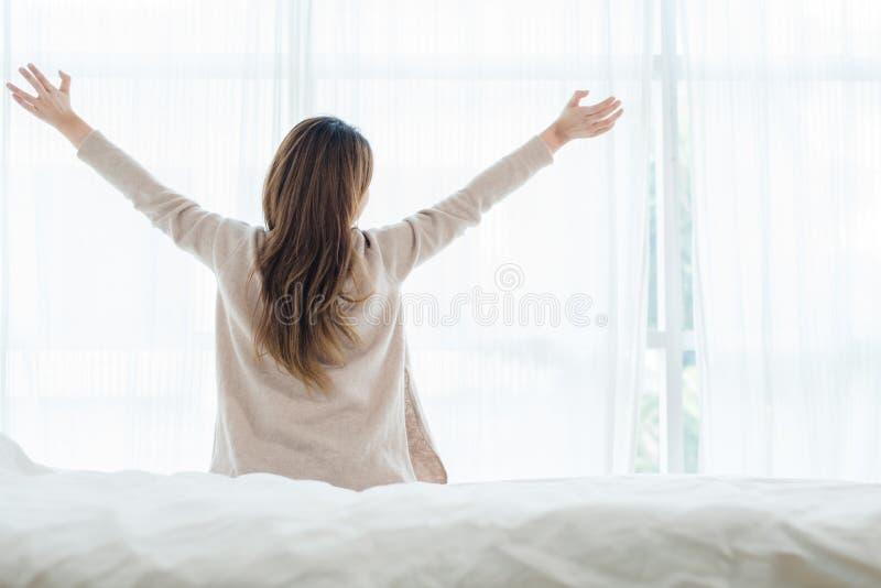 Opinião traseira a mulher asiática nova bonita feliz que acorda na manhã, sentando-se na cama, esticando no quarto acolhedor fotografia de stock