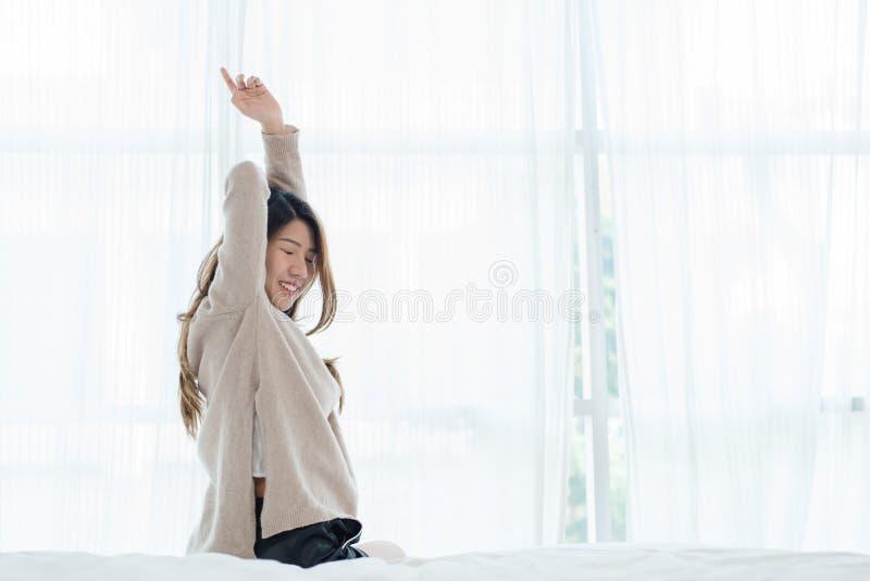 Opinião traseira a mulher asiática nova bonita feliz que acorda na manhã, sentando-se na cama, esticando no quarto acolhedor imagem de stock