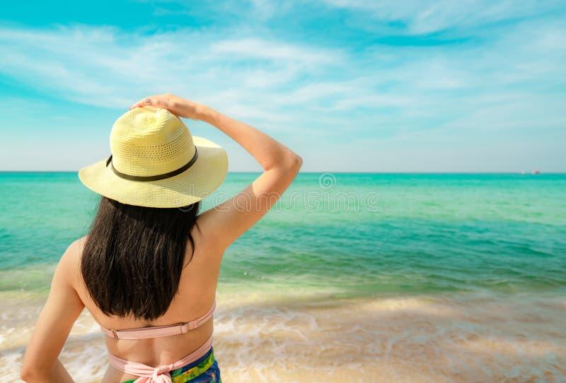 Opinião traseira a mulher asiática nova feliz com chapéu de palha para relaxar e apreciar o feriado na praia tropical do paraíso  fotos de stock royalty free