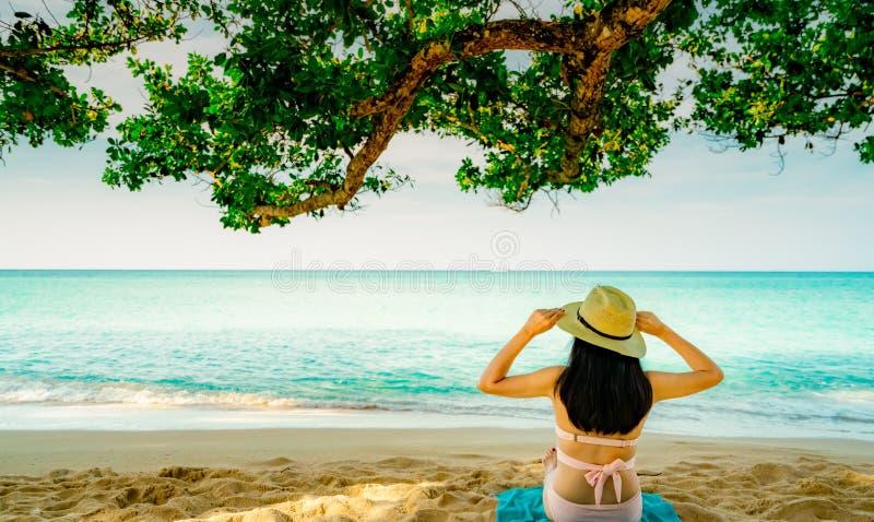 Opinião traseira a mulher asiática nova feliz no chapéu cor-de-rosa do roupa de banho e de palha para relaxar e apreciar o feriad imagens de stock