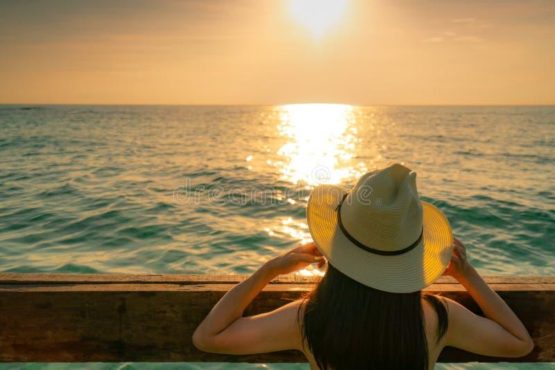 Opinião traseira a mulher asiática 'sexy' do cabelo longo preto com chapéu de palha para relaxar e apreciar o feriado no por do s imagens de stock