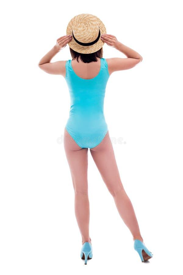 Opinião traseira a mulher bonita nova no levantamento azul do chapéu do roupa de banho e de palha isolada no branco imagem de stock royalty free