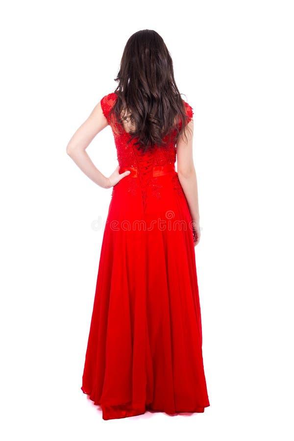 Opinião traseira a mulher bonita nova no vestido vermelho isolado no whit imagens de stock