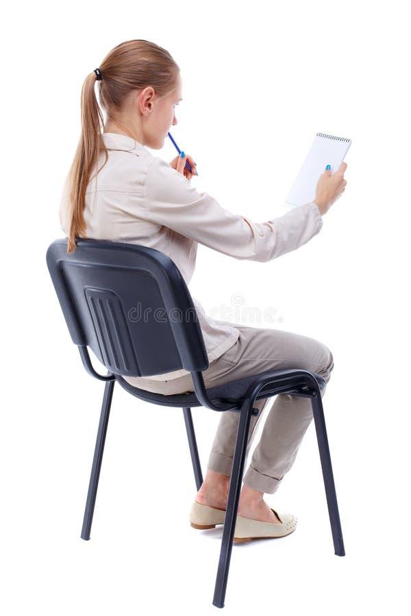 Opinião traseira a mulher bonita nova que senta-se na cadeira e nas tomadas imagem de stock