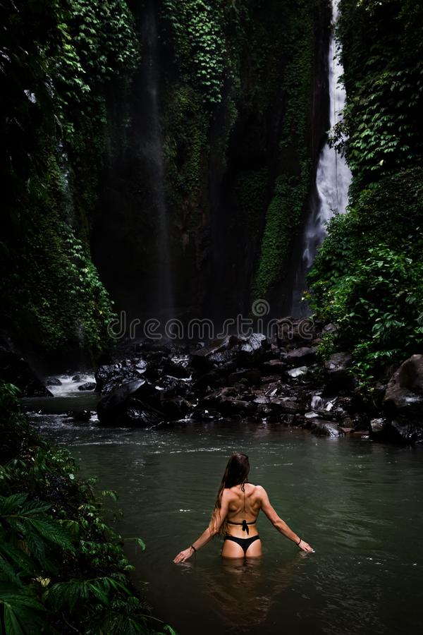 Opinião traseira a mulher bonita que banha-se e que relaxa na piscina natural antes da cachoeira no parque natural em tropical fotos de stock royalty free