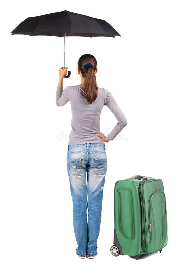 Opinião traseira a mulher com o guarda-chuva que viaja com suitcas fotos de stock