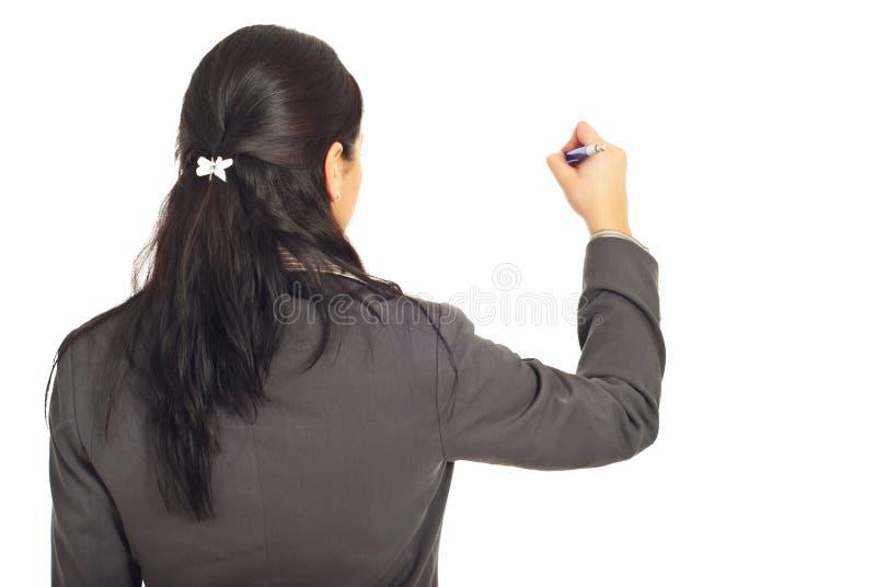 A opinião traseira a mulher corporativa escreve na cópia imagem de stock royalty free