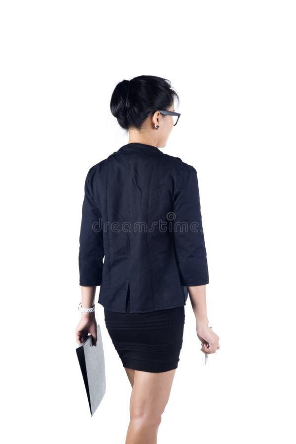 Opinião traseira a mulher de negócio que guardara o dobrador e a pena. fotografia de stock royalty free