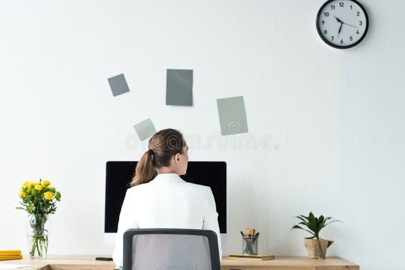 opinião traseira a mulher de negócios no local de trabalho com tela de computador fotos de stock