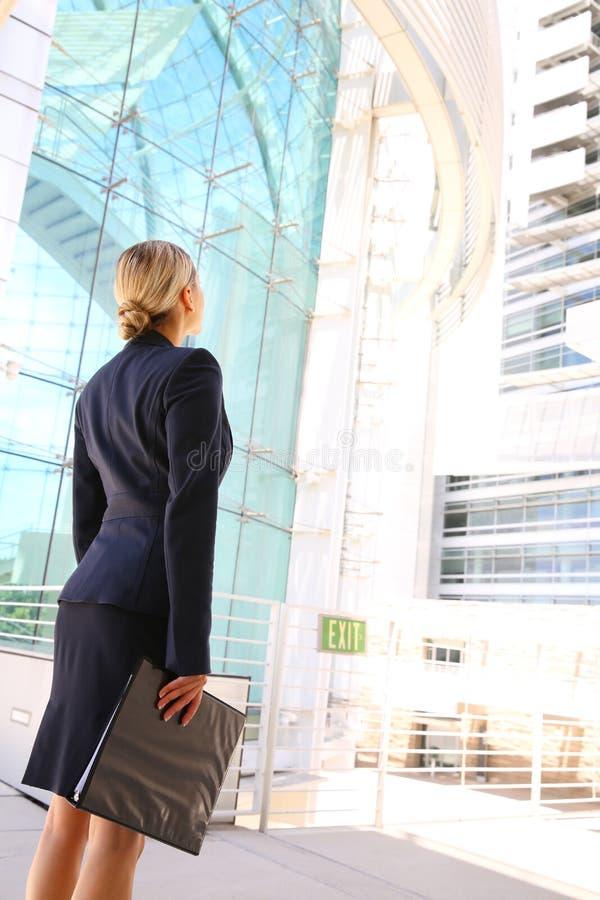Opinião traseira a mulher de negócios que olha a construção do negócio fotos de stock
