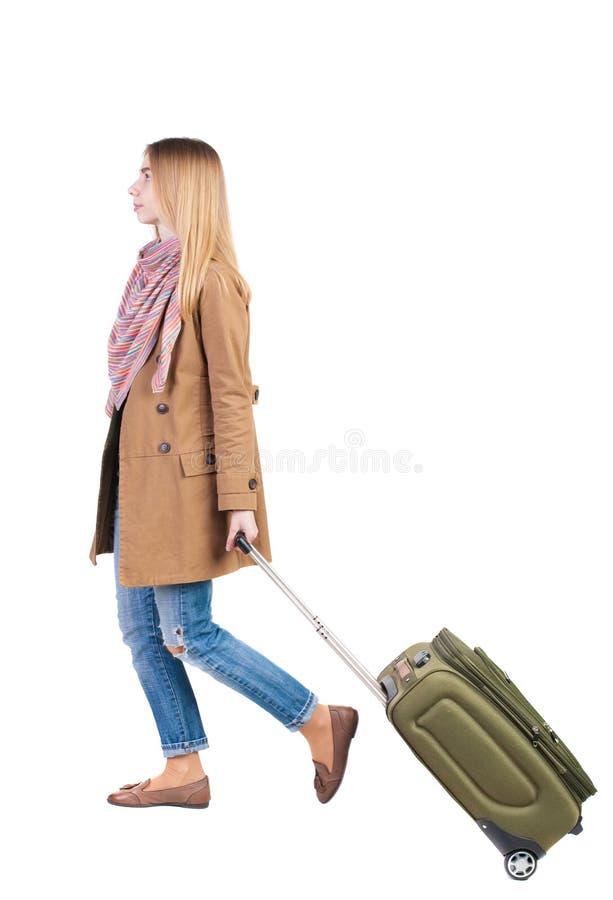 Opinião traseira a mulher de passeio com mala de viagem menina bonita no mo imagem de stock
