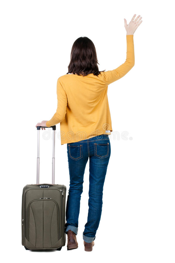 Opinião traseira a mulher de passeio no casaco de lã com boas vindas da mala de viagem fotografia de stock royalty free