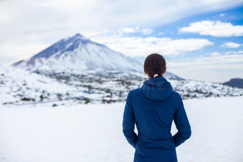 A opinião traseira a mulher do viajante aprecia montanhas da neve imagens de stock royalty free