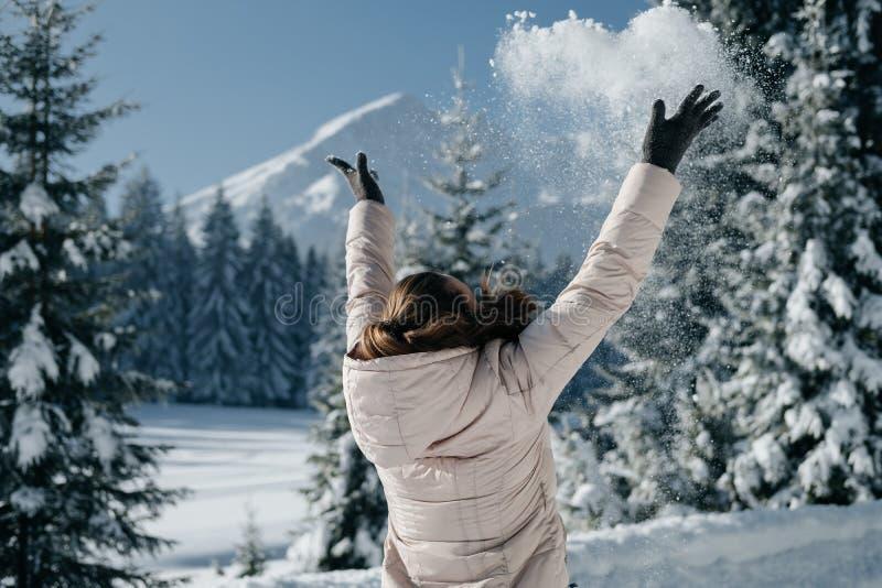 A opinião traseira a mulher em um revestimento bege do inverno joga a neve no b foto de stock