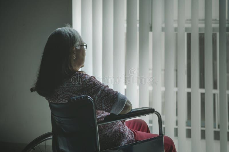 Opinião traseira a mulher envelhecida que olha para fora a janela imagens de stock