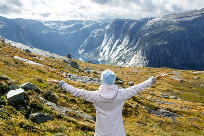 Opinião traseira a mulher feliz que aprecia a liberdade com os braços extendidos dentro imagens de stock