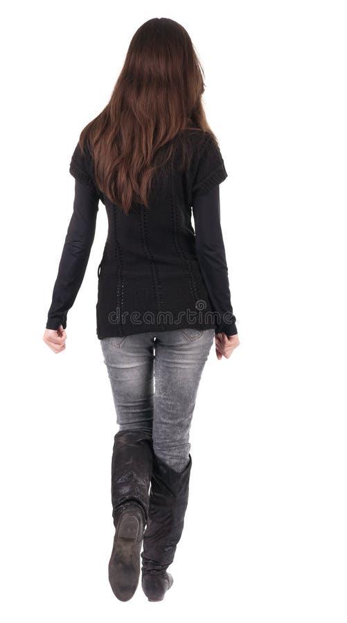 Opinião traseira a mulher indo nas calças de brim e na camiseta fotografia de stock