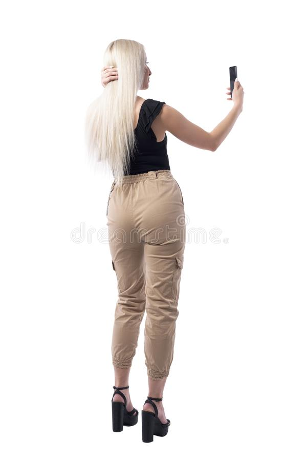 Opinião traseira a mulher loura 'sexy' segura que ajusta o cabelo e que toma autorretratos com telefone celular imagem de stock