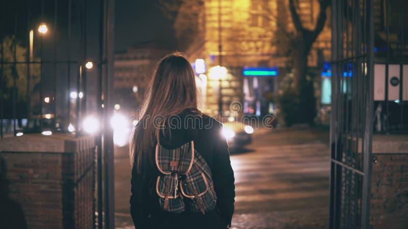 Opinião traseira a mulher moreno nova que anda tarde na noite centro de cidade em Roma, Itália As voltas da menina e consideram o fotografia de stock royalty free