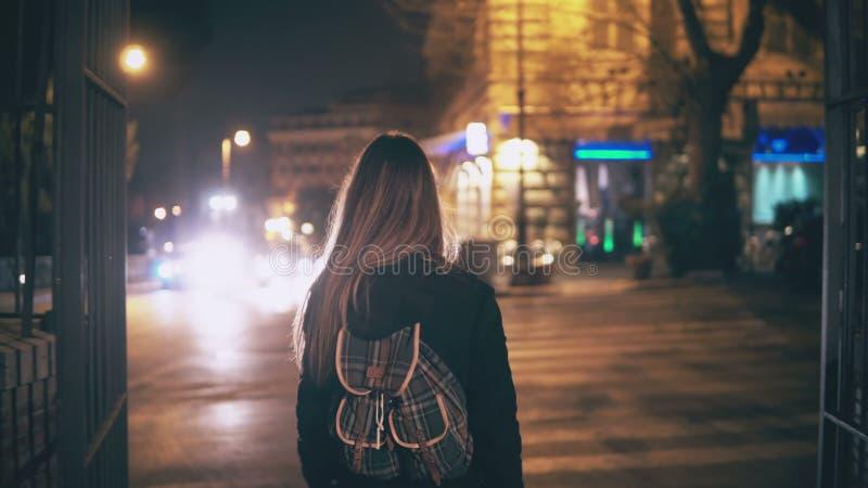 Opinião traseira a mulher moreno nova que anda tarde na noite centro de cidade em Roma, Itália As voltas da menina e consideram o imagens de stock royalty free