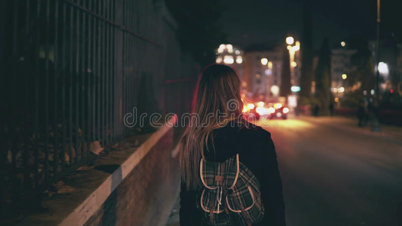 Opinião traseira a mulher moreno que anda perto da estrada no tempo do tráfego A menina atravessa a cidade tarde na noite apenas foto de stock royalty free