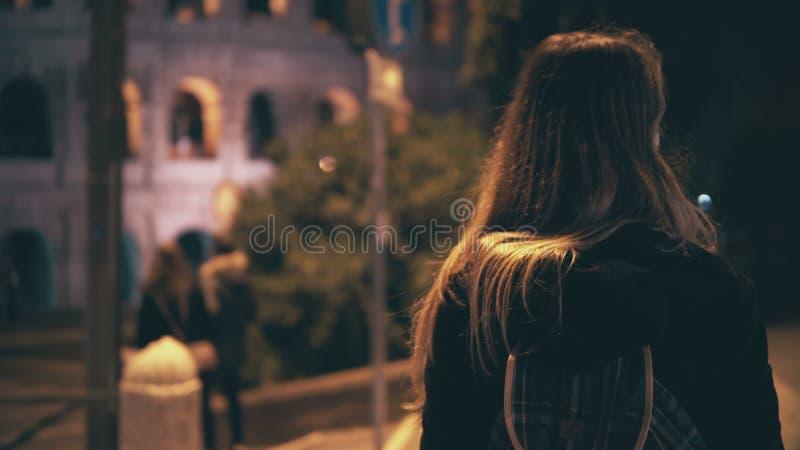 Opinião traseira a mulher moreno que anda tarde na noite em Roma, Itália Cruz da menina a estrada na faixa de travessia perto do  fotos de stock
