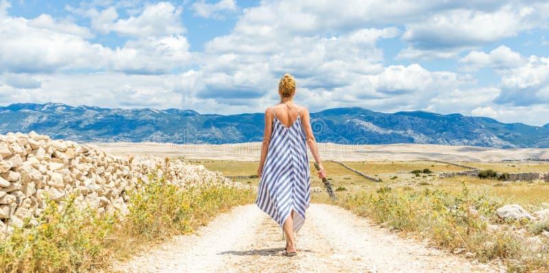 Opinião traseira a mulher no ramalhete da terra arrendada do vestido do verão de flores da alfazema ao andar exterior com rochoso imagens de stock