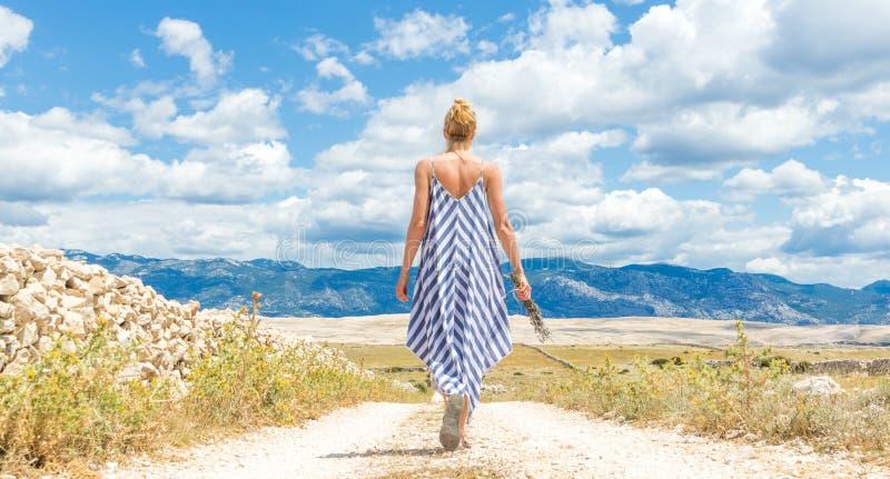 Opinião traseira a mulher no ramalhete da terra arrendada do vestido do verão de flores da alfazema ao andar exterior com rochoso imagens de stock royalty free