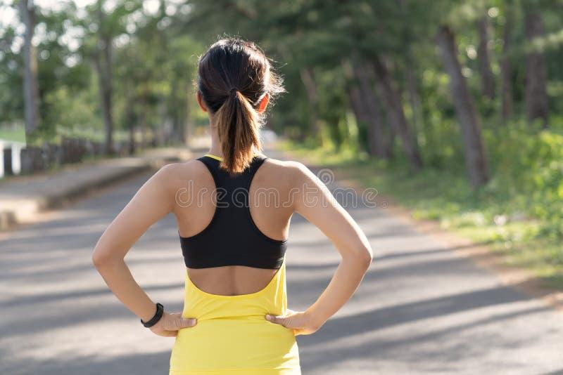Opinião traseira a mulher nova da aptidão que corre na estrada na manhã, nos povos e no conceito do esporte, foco seletivo fotos de stock