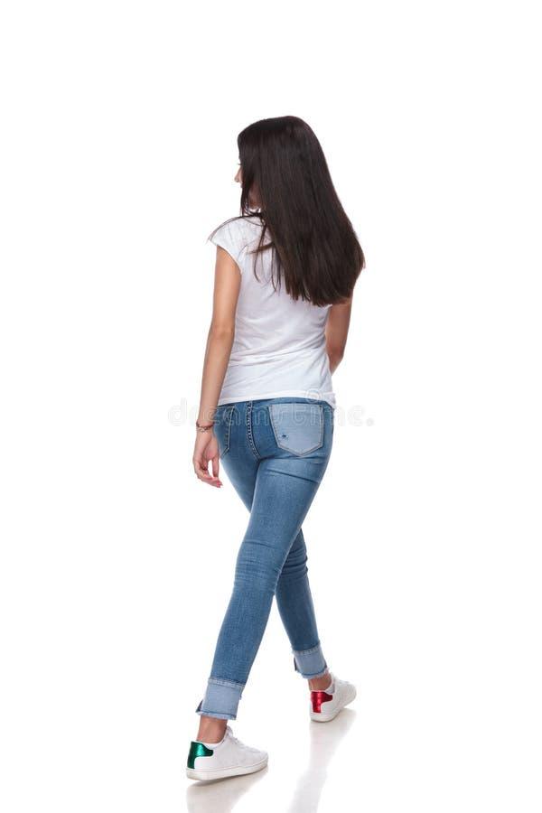 Opinião traseira a mulher ocasional que anda e que olha para tomar partido imagens de stock