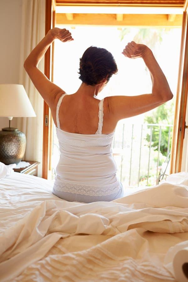 Opinião traseira a mulher que acorda na cama na manhã imagem de stock
