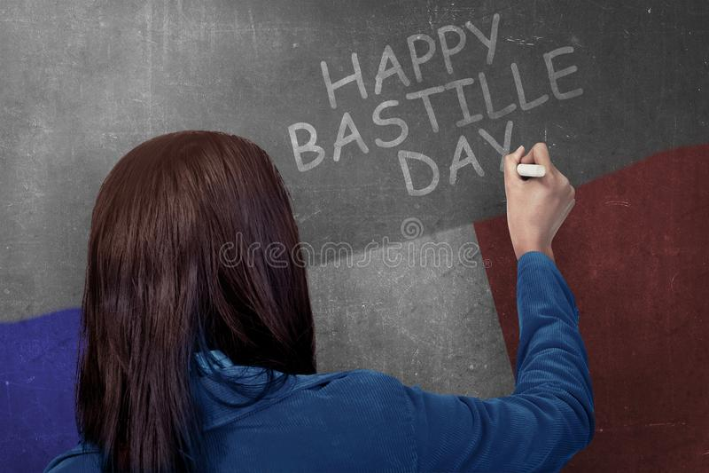 Opinião traseira a mulher que escreve o dia de bastille feliz na parede imagens de stock royalty free