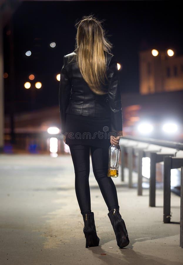 Opinião traseira a mulher que levanta na estrada na noite fotos de stock