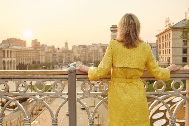 Opinião traseira a mulher que olha o panorama de nivelar a cidade Fêmea adulta na capa de chuva amarela exterior, espaço da cópia fotografia de stock