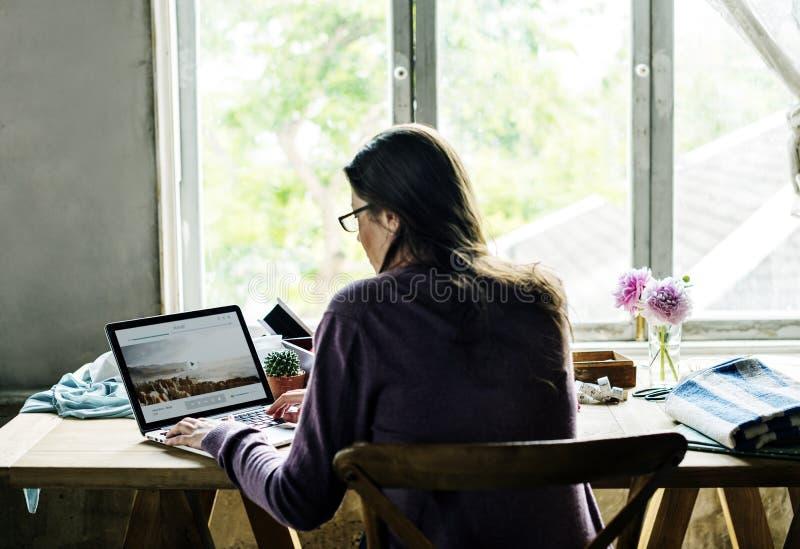 Opinião traseira a mulher que trabalha no portátil do computador na tabela de madeira imagem de stock