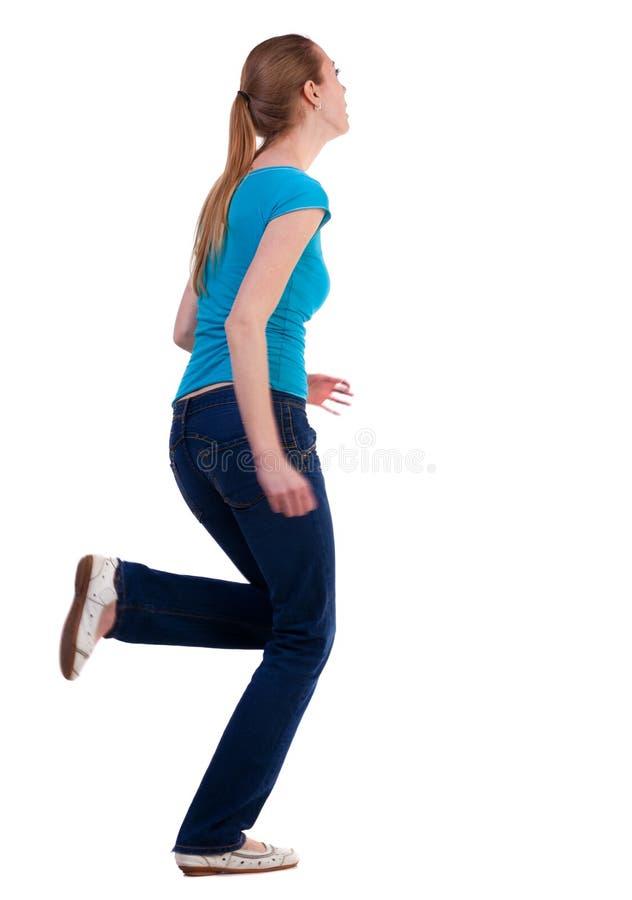 Opinião traseira mulher running nas calças de brim foto de stock