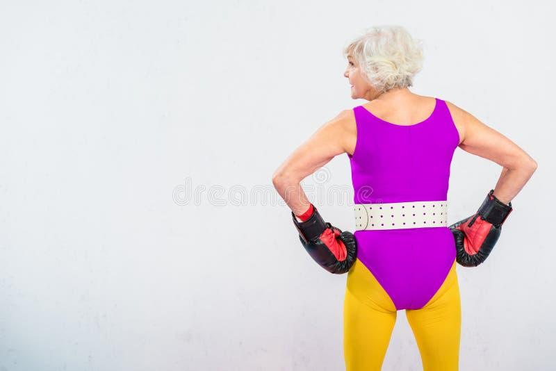 opinião traseira a mulher superior desportiva nas luvas de encaixotamento que estão com mãos na cintura imagens de stock