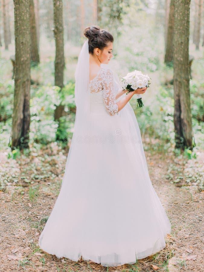Opinião traseira a noiva bonita no vestido de casamento longo que guarda o ramalhete das peônias Lugar da floresta foto de stock royalty free