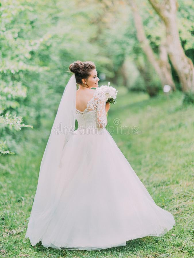 A opinião traseira a noiva encantador que guarda o ramalhete do casamento durante a caminhada na floresta foto de stock