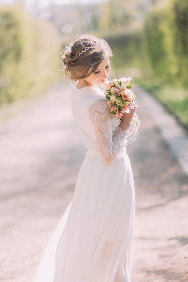 Opinião traseira a noiva loura nova no vestido branco que olha o ramalhete nupcial exterior foto de stock