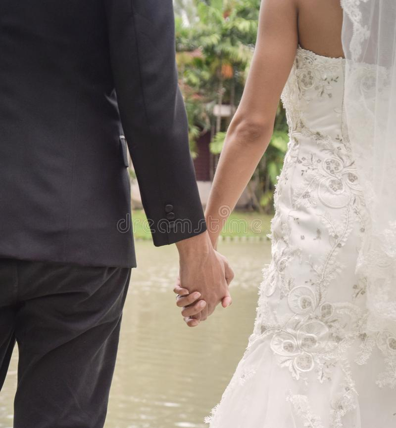 Opinião traseira a noiva no vestido e no noivo brancos no terno que guarda o tema do casamento das mãos seriamente foto de stock