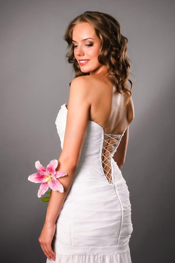 Opinião traseira a noiva nova de sorriso com uma flor imagem de stock royalty free