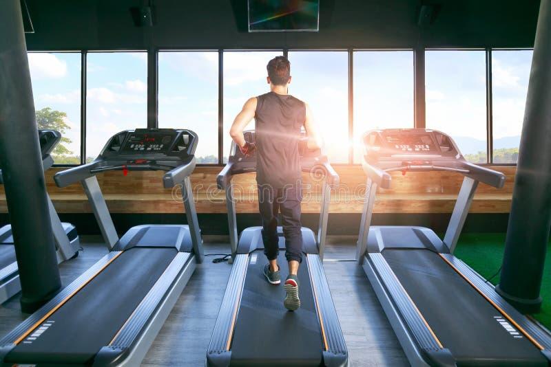 Opinião traseira o atleta do homem novo com corrida na escada rolante no gym imagens de stock