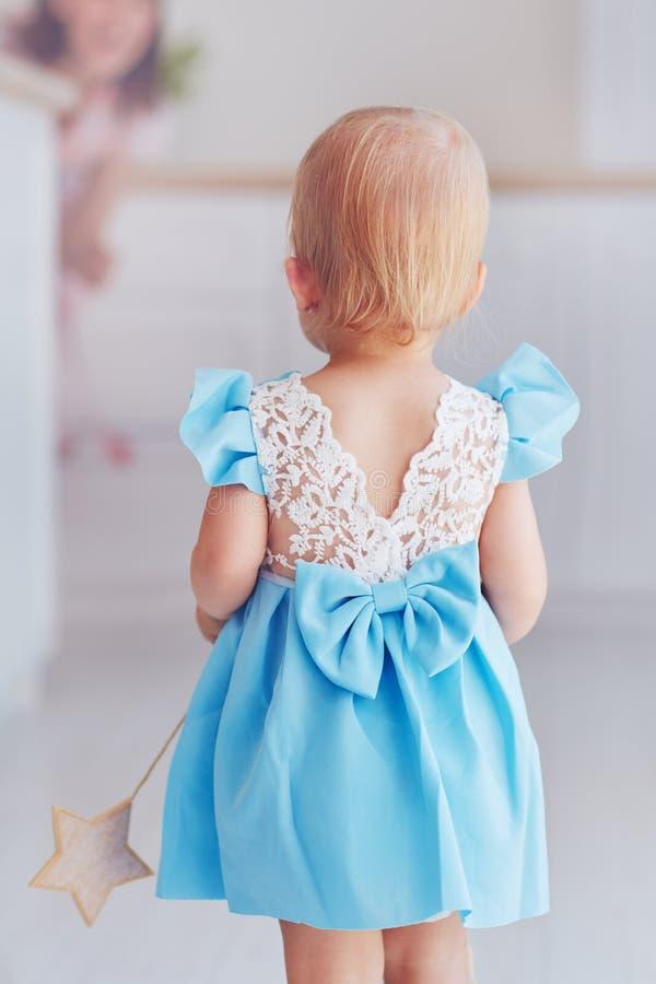 Opinião traseira o bebê pequeno bonito no vestido de partido azul do laço imagem de stock royalty free
