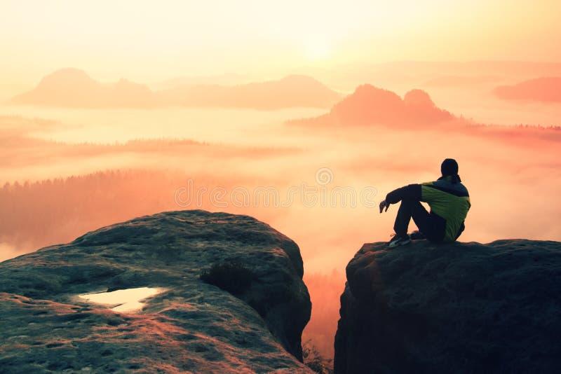 Opinião traseira o caminhante masculino que senta-se no pico rochoso ao apreciar uma aurora colorida acima do vale dos mounrains fotografia de stock royalty free