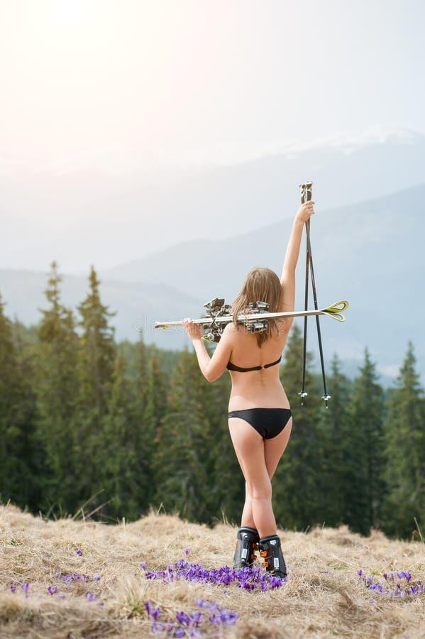 A opinião traseira o esquiador 'sexy' da menina está apreciando a mola morna, o terno de natação vestindo, as botas e os óculos d foto de stock royalty free