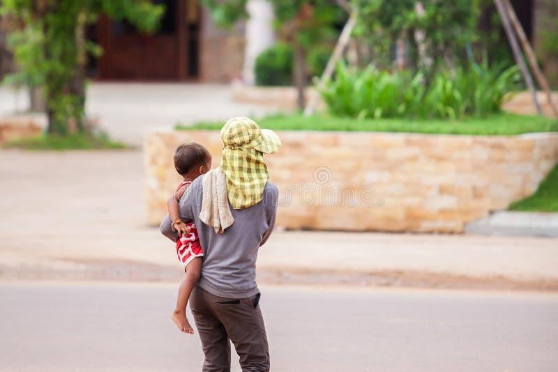 Opinião traseira o filho da terra arrendada da mãe do Khmer em seus braços quando através de uma rua perto do canteiro de obras P imagens de stock royalty free