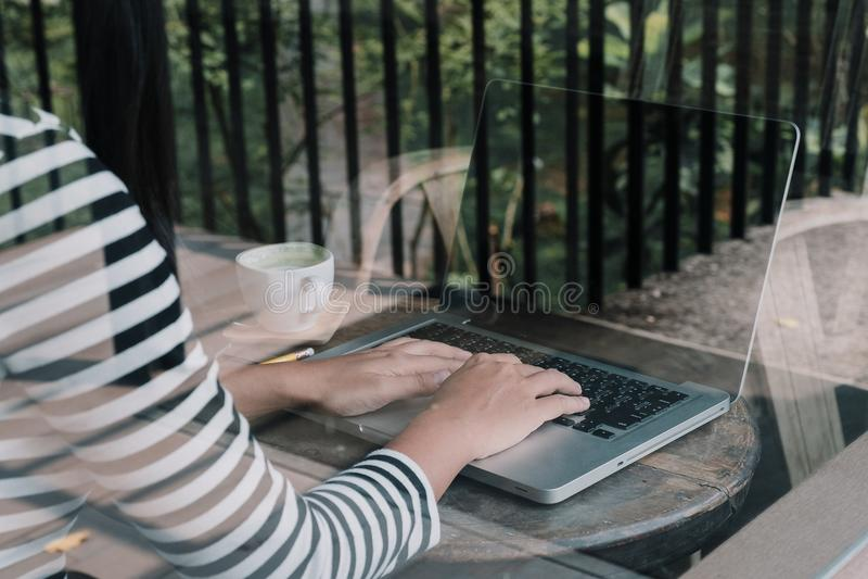 A opinião traseira o freelancer da mulher está trabalhando e entrega o keyboa de datilografia imagem de stock royalty free