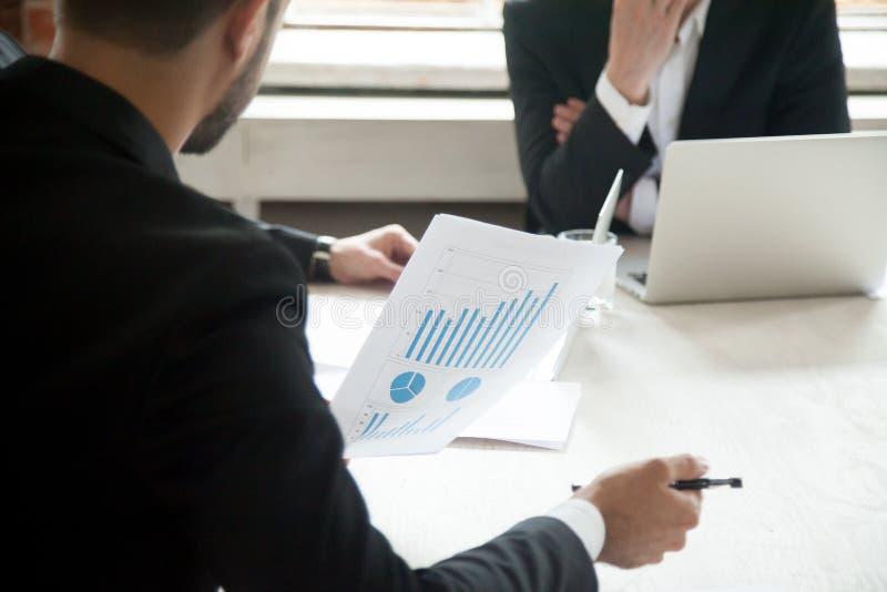 Opinião traseira o gerente que guarda o relatório financeiro com gráfico de aumentação imagem de stock